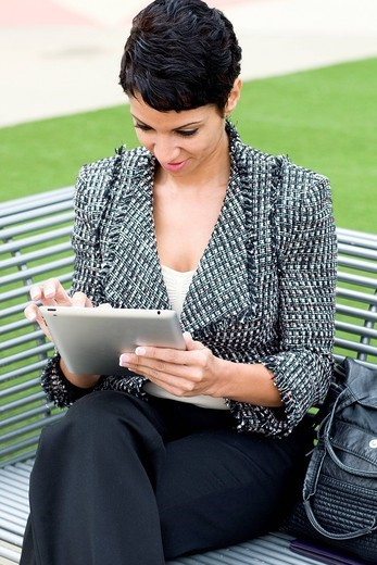 Cape Verdean businesswoman using tablet computer outdoors : Stock Photo