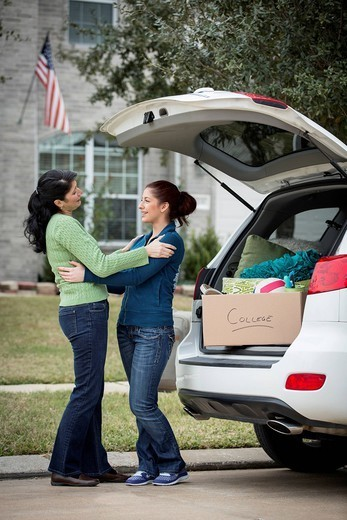 Hispanic mother helping daughter pack for college : Stock Photo