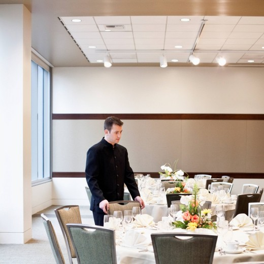 Caucasian waiter setting tables in dining room : Stock Photo