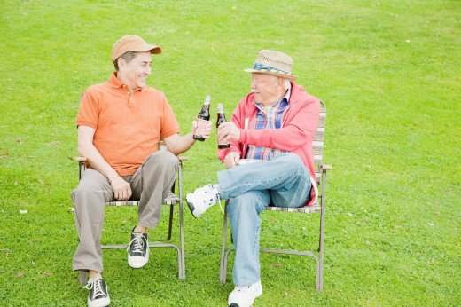 Older men drinking beer outdoors : Stock Photo