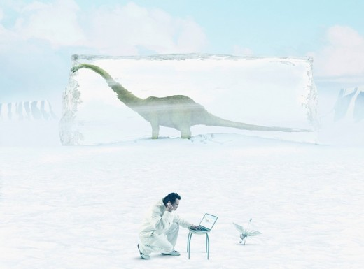 Asian man with laptop in front of dinosaur frozen in ice : Stock Photo