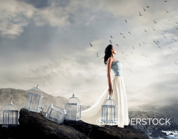 Stock Photo: 1589-66035 Hispanic woman on cliff with empty birdcages