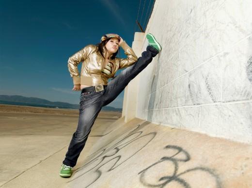 Asian woman stretching leg on wall : Stock Photo