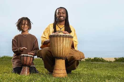 African father and son playing drums : Stock Photo