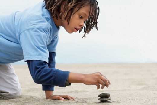 Mixed Race boy stacking stones on sand : Stock Photo