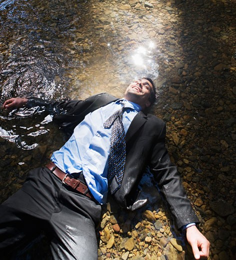 Hispanic businessman laying in water : Stock Photo