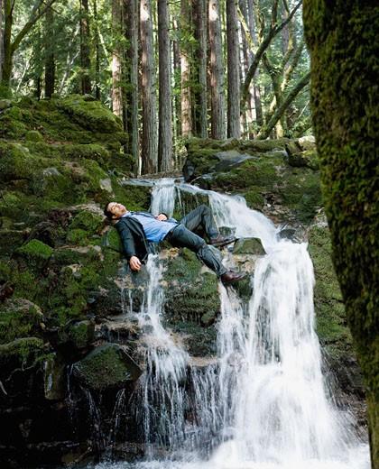 Hispanic businessman laying on waterfall : Stock Photo