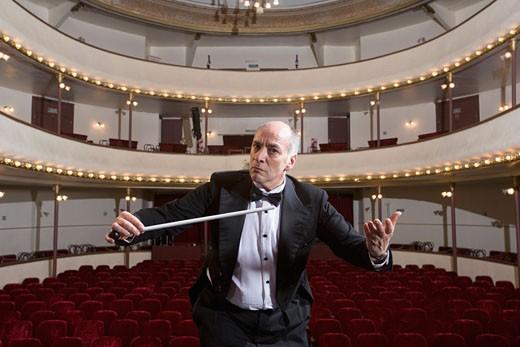 Hispanic male conductor in empty theater : Stock Photo