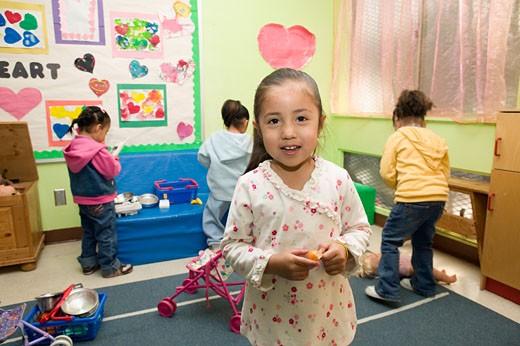 Hispanic girl in classroom play area : Stock Photo