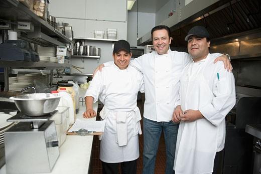 Hispanic chef and kitchen workers in kitchen : Stock Photo