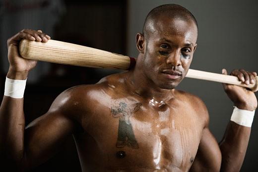 Sweating African baseball player holding bat : Stock Photo