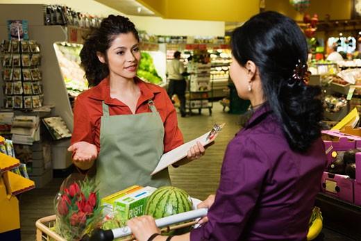 Hispanic clerk helping shopper in grocery store : Stock Photo