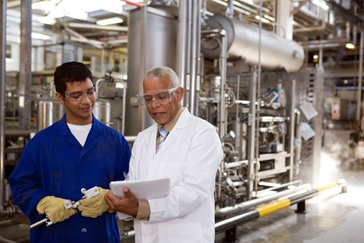 Scientist talking to factory worker : Stock Photo