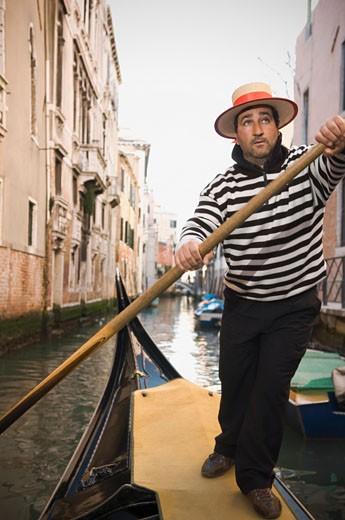 Italian gondolier rowing gondola through canal : Stock Photo