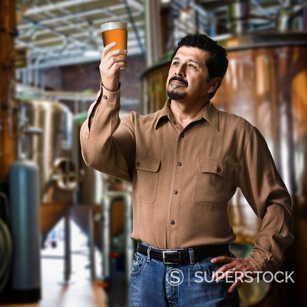 Stock Photo: 1589-66769 Hispanic man examining pint of beer in brewery