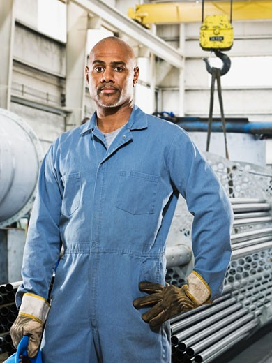African man in gloves and coveralls in factory : Stock Photo