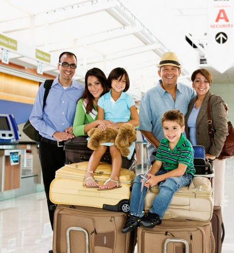 Hispanic family posing with luggage in airport : Stock Photo