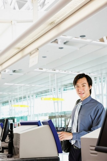 Asian businessman checking in at airport : Stock Photo