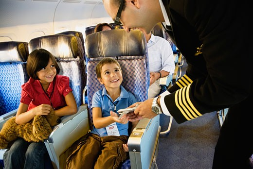 Flight attendant helping children on airplane : Stock Photo