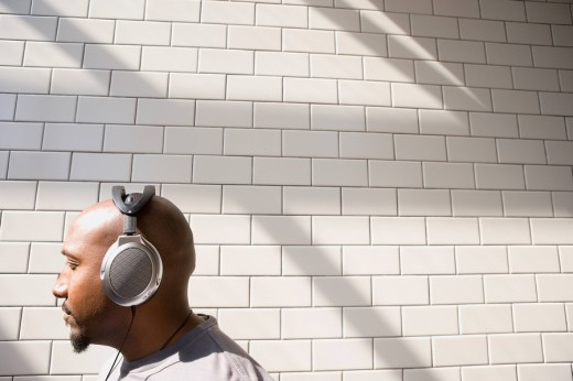 African man listening to headphones in urban setting : Stock Photo