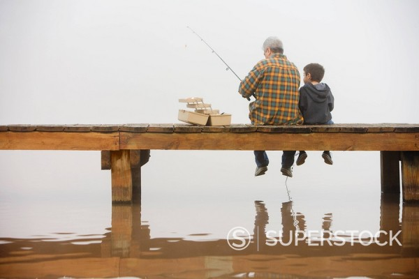 Grandfather and grandson fishing off dock : Stock Photo