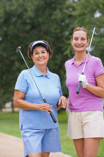 Mature woman holding golf clubs : Stock Photo