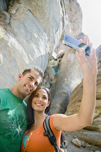 Hispanic couple taking photographs with cell phone : Stock Photo