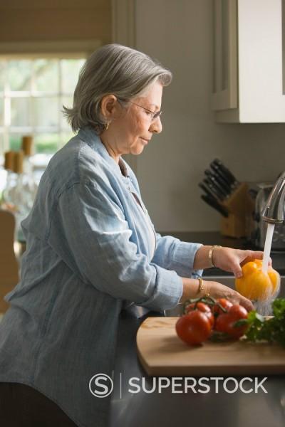 Stock Photo: 1589-67114 Senior Hispanic woman washing fresh vegetables