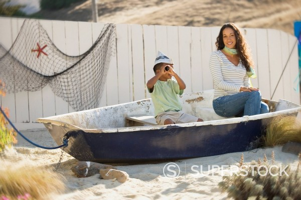 Stock Photo: 1589-67157 Mixed race mother and son pretending to sail in a boat