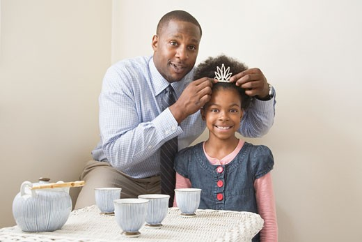 African father and daughter posing with tiara : Stock Photo