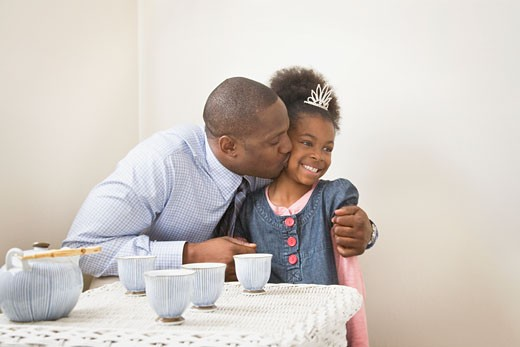 African father kissing daughter with tiara : Stock Photo