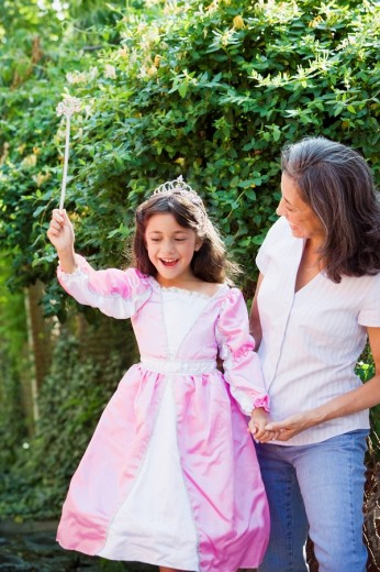 Hispanic grandmother with granddaughter wearing princess costume : Stock Photo