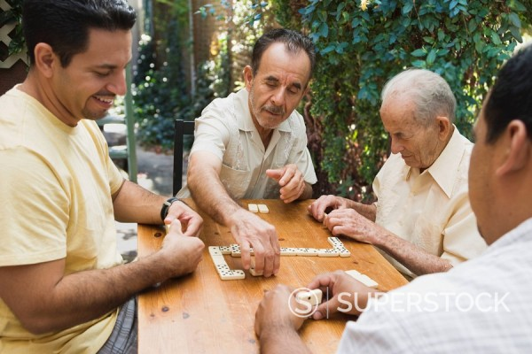 Hispanic men playing dominos on patio : Stock Photo