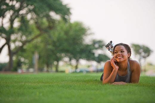 Mixed race woman laying on grass using cell phone : Stock Photo