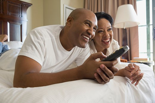 African couple in bed watching television : Stock Photo