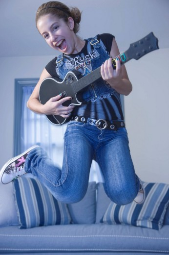 Mixed race girl jumping in livingroom with guitar : Stock Photo