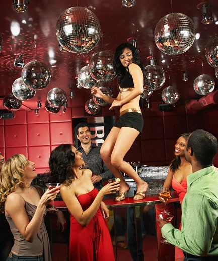 People watching woman dancing on bar in nightclub : Stock Photo