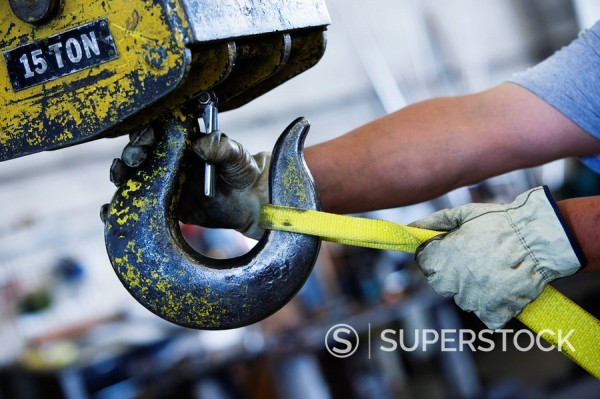 Worker attaching rope to large hook in warehouse : Stock Photo