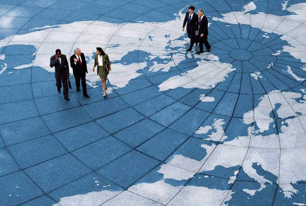 Businesspeople walking on map of globe : Stock Photo