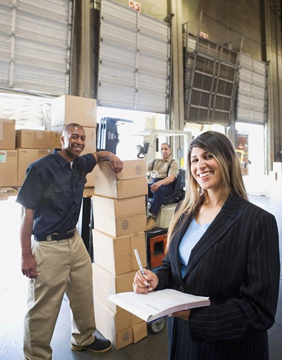 Warehouse workers with boxes and forklift : Stock Photo