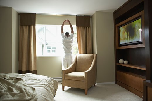 Man stretching and looking out window : Stock Photo