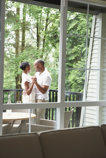 View through window to couple dancing on deck : Stock Photo