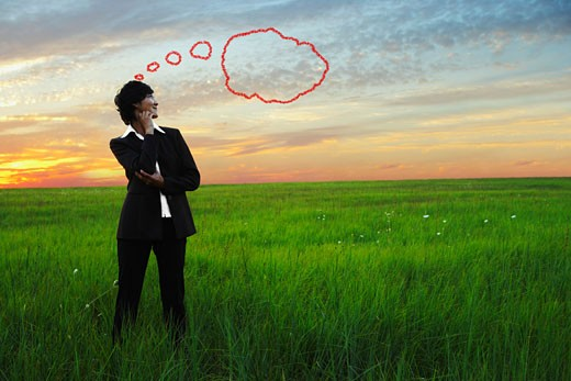 Kazakh businesswoman in field with thought bubble : Stock Photo