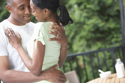 African couple hugging and smiling at each other outdoors : Stock Photo