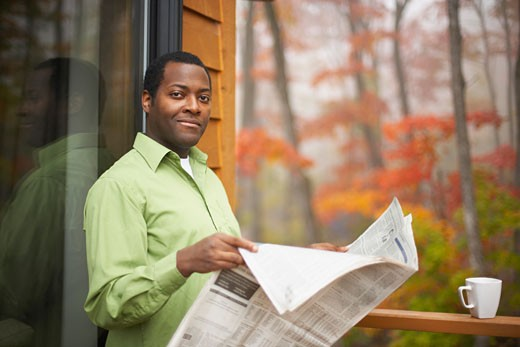 African man reading newspaper outdoors : Stock Photo