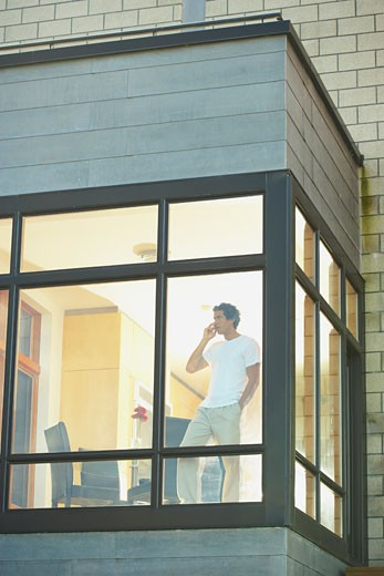 Man talking on cell phone next to window : Stock Photo