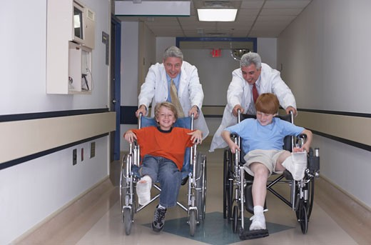 Two boys with casts in wheelchair race : Stock Photo