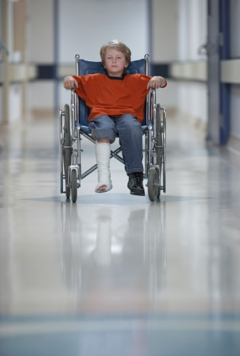 Boy with cast in wheelchair : Stock Photo