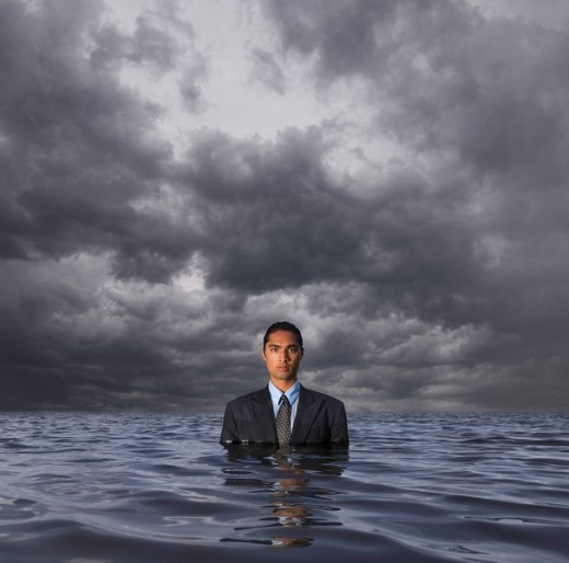 Hispanic businessman standing in water : Stock Photo