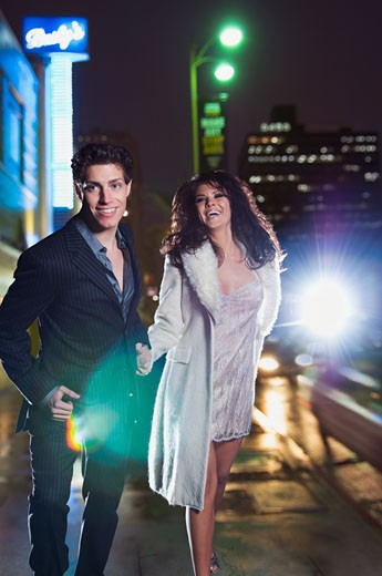 Elegant couple walking on urban street at night : Stock Photo